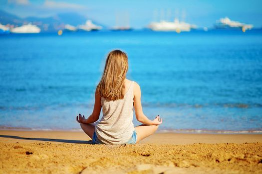 Beautiful young girl enjoying her vacation by the sea