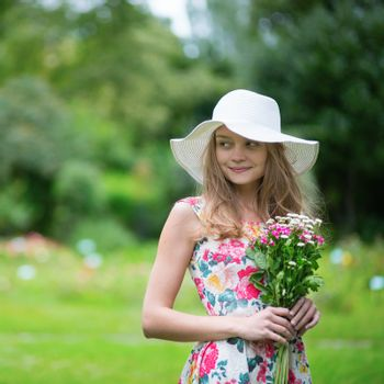 Beautiful young girl in white hat holding flowers