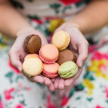 Girl holding colorful French macaroons in hands