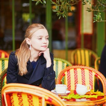 Beautiful young woman drinking coffee and eating delicious fresh croissant in Parisian outdoor cafe