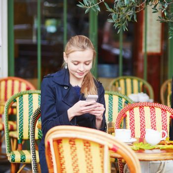 Beautiful young woman drinking hot chocolate in Parisian outdoor cafe and taking photo with her mobile phone