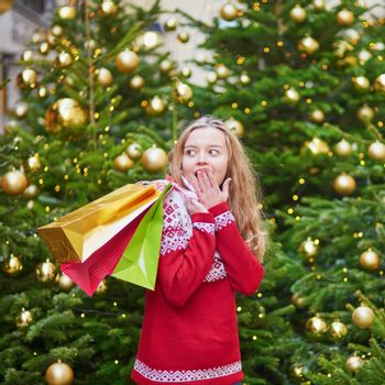 Cheerful young girl with colorful shopping bags near Christmas tree