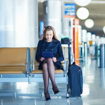 Young woman in international airport reading a book on tablet while waiting for her flight