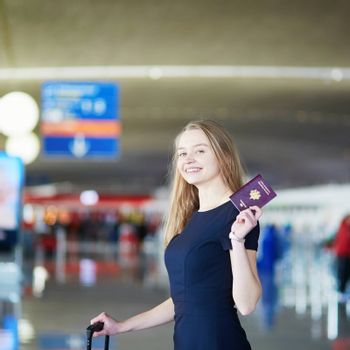 Young woman in international airport, holding French passport and looking happy