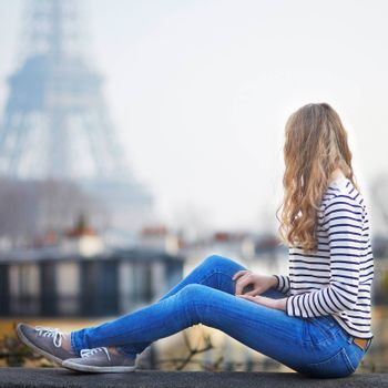 Happy young woman in Paris, near the Eiffel tower. Tourist in France, enjoying city view