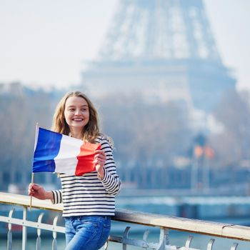 Beautiful young girl with French national tricolor flag near the Eiffel tower
