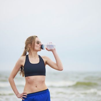 Healthy fitness runner girl drinking water from plastic bottle on running break. Young European woman on beach cardio training taking a rest during workout. Healthy lifestyle, sport and hydration concept