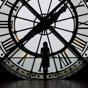 Woman silhouette standing in front of clock in the Orsay Museum, Paris, France. Unrecognizable person overlooking Paris