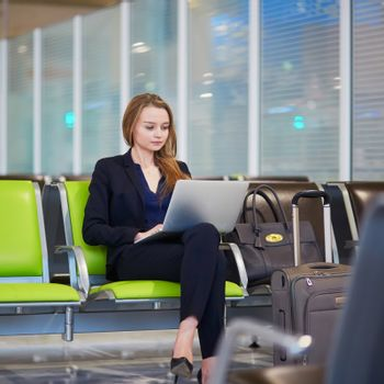 Young woman in international airport working on laptop while waiting for her flight