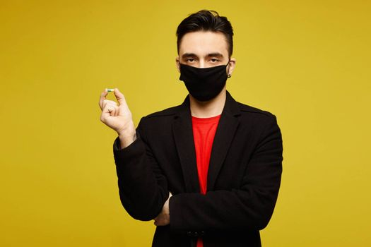 Handsome man in black coat and black protective mask keeps a pill in his hand and posing at the yellow background, isolated. Medicine for viruses. Healthcare lifestyle. Young man wearing a protective mask to prevent infection and airborne respiratory illness