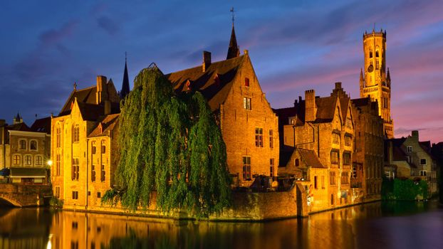 Panorama of Bruges tourist landmark attraction - Rozenhoedkaai canal with Belfry and old houses along canal with tree in the night. Brugge, Belgium