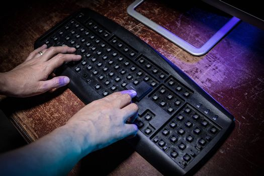 Broken keyboard with hammer on wooden table. Keyboard with no keys on dark desktop. Woman finger on Enter button. Only one workable button on keyboard