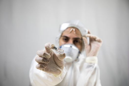 Coronavirus covid 19 infected blood vial in hand of female doctor with surgical mask and glows. Coronavirus covid 19 reseach laboratory, coronavirus covid-19 vaccine research. Selective focus