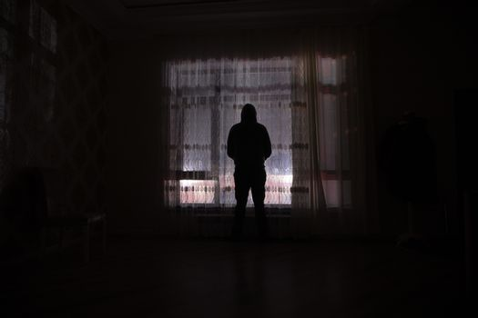 Silhouette of a man standing at a window inside the room. Dark mood conceptual image
