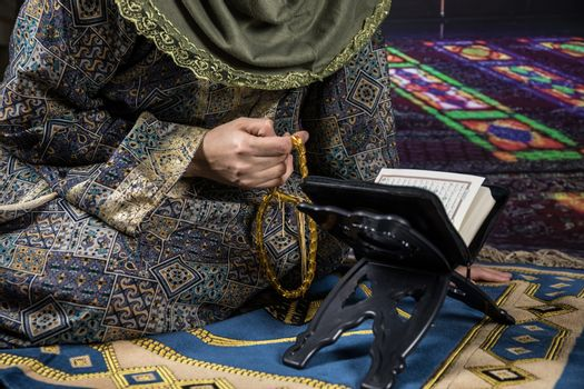Muslim woman praying for Allah muslim god at the mosque. Hands of muslim woman on the carpet praying in traditional wearing clothes, Woman in Hijab.