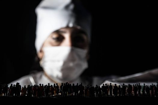 Woman doctor in mask looking at crowd. Virus, outbreak and mass disease, Corona virus concept. Selective focus. Creative artwork decoration