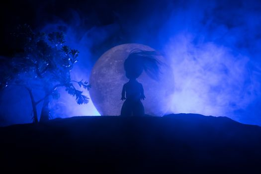 Girl standing alone behind big full moon. Dark toned foggy background. Loneliness bad mood concept