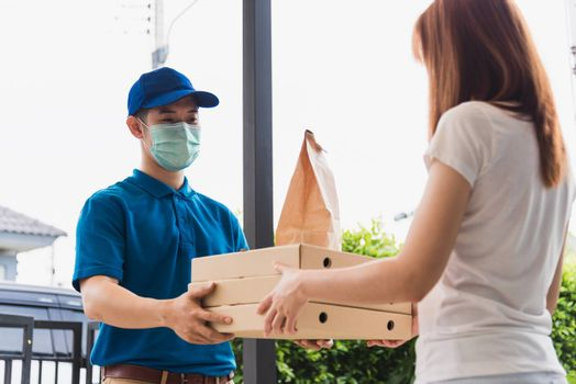 Asian delivery express courier young man giving paper bags fast food and pizza box to woman customer receiving both protective face mask, under curfew quarantine pandemic coronavirus COVID-19