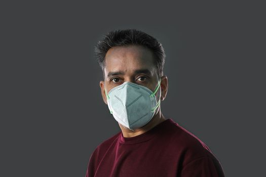 Indian Man wearing a N95 mask for protection against virus, dust, pollution and smog