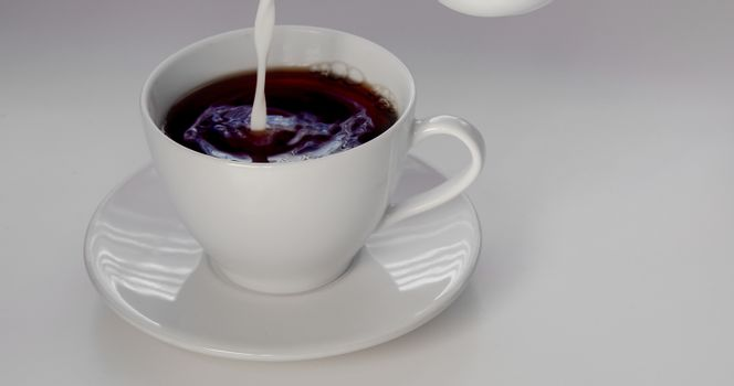 Pouring cream on an cup of coffee on a white background