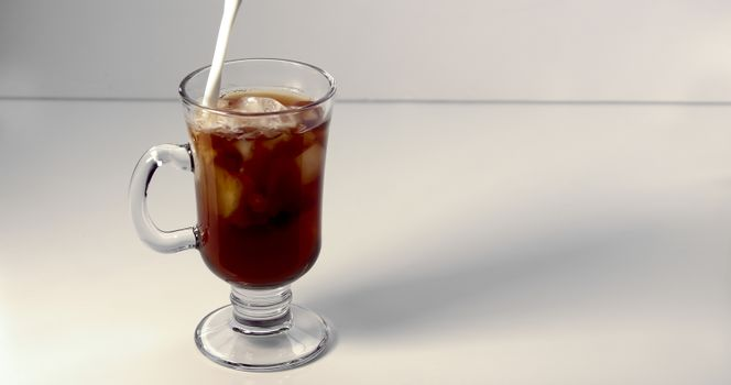 Pouring cream on an ice coffee cup on a white background