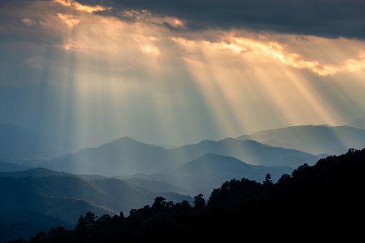 Ray of sunlight shining through cloudy sky to blue mountains, Huay Namdung, Chiangmai, Thailand.
