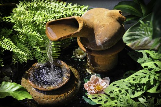 Cascading terracotta garden feature in a small courtyard patio setting, with lush tropical greenery, ferns and water lillies.