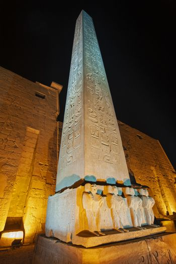 Large obelisk with statues at entrance pylon to ancient egyptian Luxor Temple lit up during night