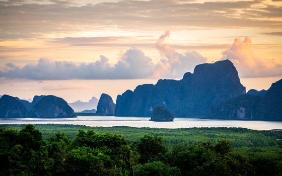 Natural scene of dark islands in Samed Nang Chee beach, Phang Nga, most attraction in Thailand at sunrise with cloudy morning sky.