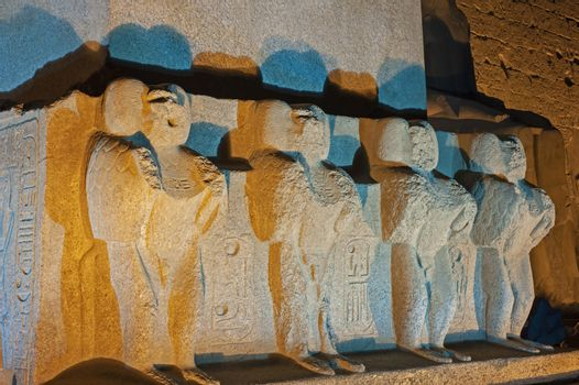 Statues on base of large obelisk at entrance pylon to ancient egyptian Luxor Temple lit up during night