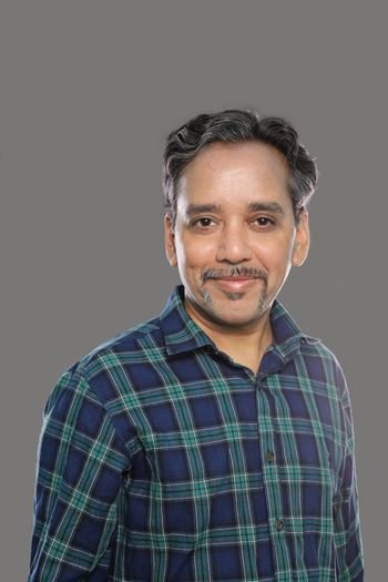 Smiling Indian Man in Casual shirt in 40s on grey background