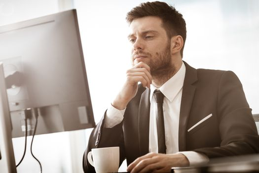 Business crisis concept. Young businessman sitting at the office table busy talking on a cell phone resolving a very serious work problem. Man in suit indoors on glass window background.