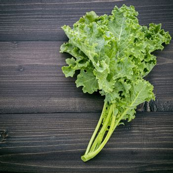Fresh organic curly kale leaves flat lay on a wooden table with