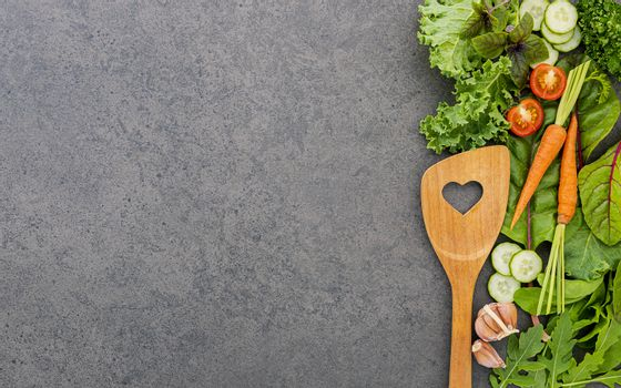 Wooden spoon and vegetables on dark stone background. Healthy fo