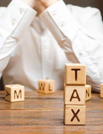 Businessman ponders the process of paying taxes and tax refunds. Tax holidays and benefits. Creating an enabling environment for business and economic growth. Protection of business and industry.