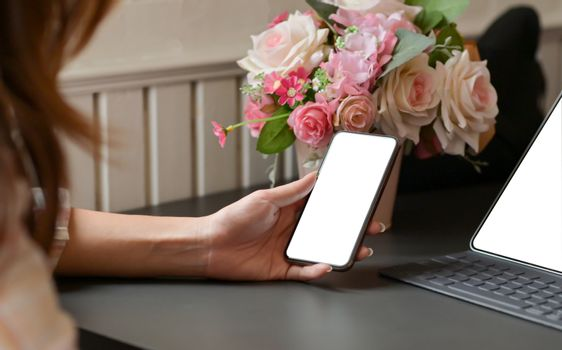 Cropped shot of A woman holding a smartphone in  hand with laptop on the desk at home office.