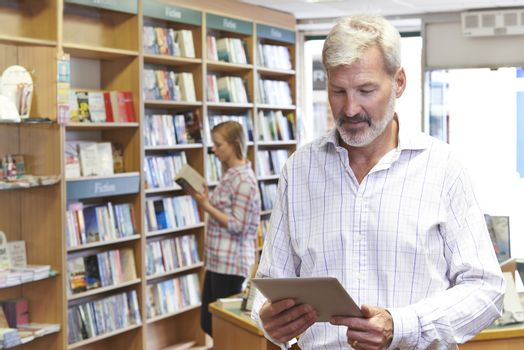 Male Bookstore Owner Using Digital Tablet With Customer In Backg