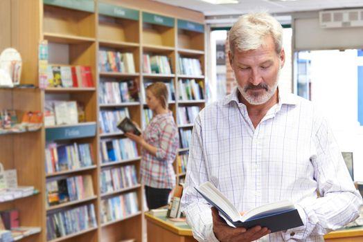 Customers Browsing Books In Bookshop