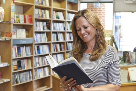 Female Customer Reading Book In Bookstore