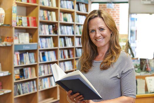Portrait Of Female Customer Reading Book In Bookstore
