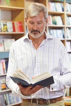 Male Customer Reading Book In Bookstore