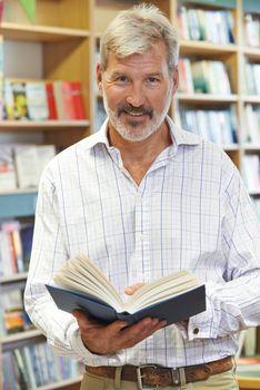 Portrait Of Male Customer Reading Book In Bookstore