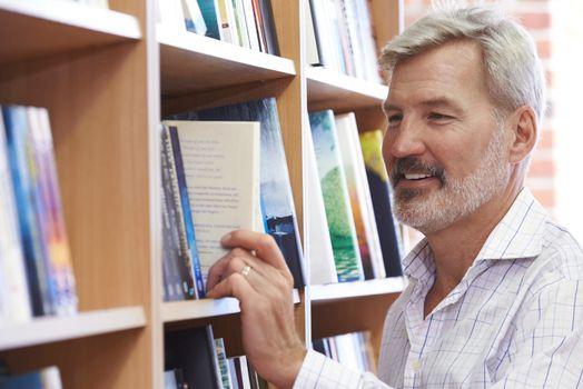 Mature Man Choosing A Book In Bookstore