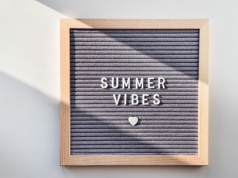 Top view on letter board with word Summer Vibes and heart. Flat