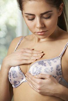 Woman Wearing Bra Examining Breast