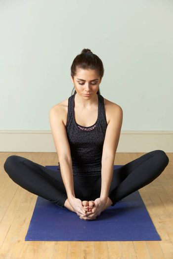Young Woman In Sportswear Meditating On Mat
