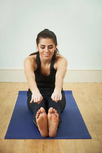 Young Woman In Sportswear Touching Toes On Mat