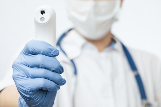Close-up shot of doctor wearing protective surgical mask ready to use infrared forehead thermometer (thermometer gun) to check body temperature for virus symptoms - epidemic virus outbreak concept