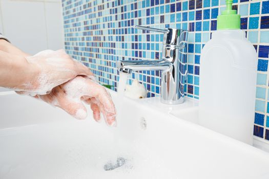 Woman diligently washing hands with antibacterial soap and water performing basic protective measures against spreading of coronavirus COVID-19 desease