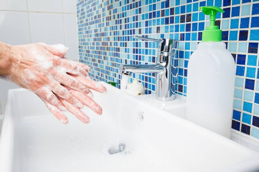 Woman washing hands with antibacterial soap and water rubbing fingers performing basic protective measures against spreading of coronavirus COVID-19 desease